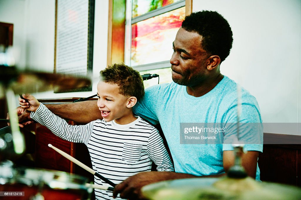 Smiling young boy playing drums with father : Foto de stock