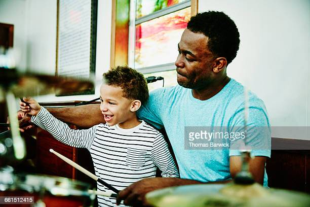 Smiling young boy playing drums with father