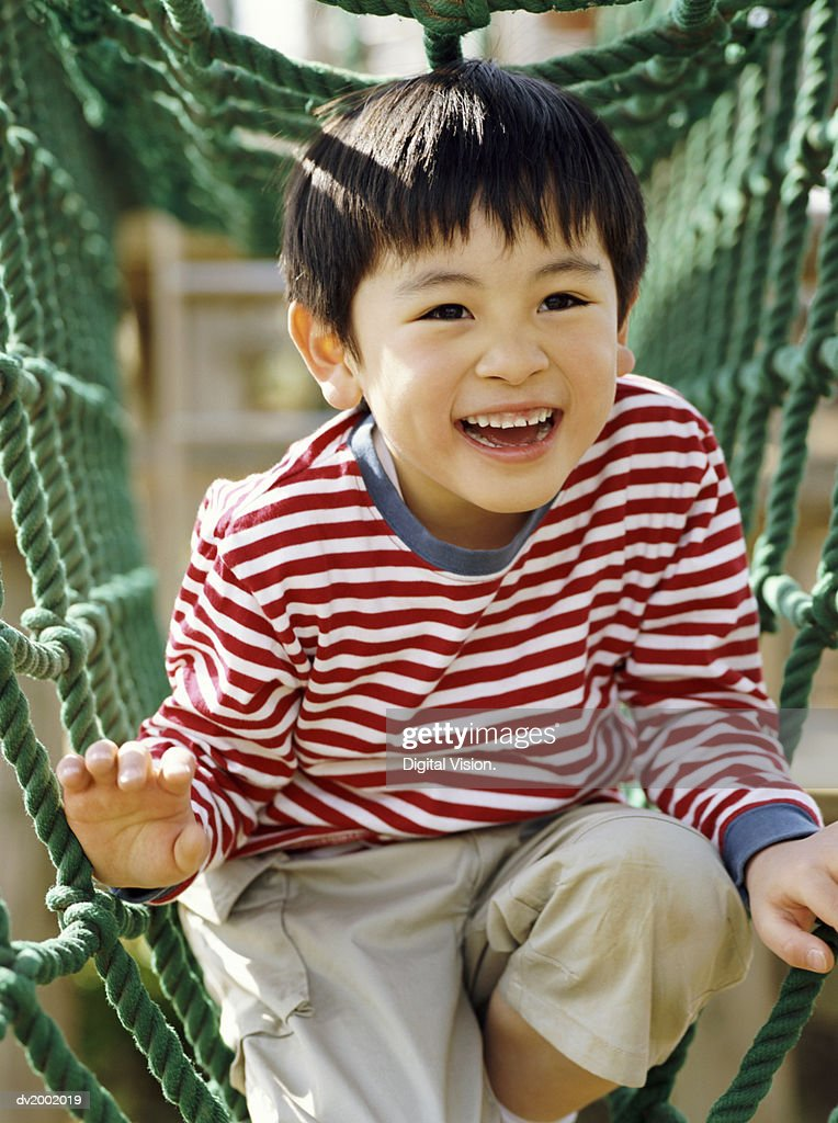 Smiling Young Boy Playing on Climbing Ropes in an Adventure Playground : Stock Photo