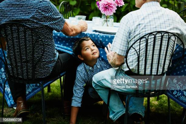 Smiling young boy playing under table during family dinner party in backyard