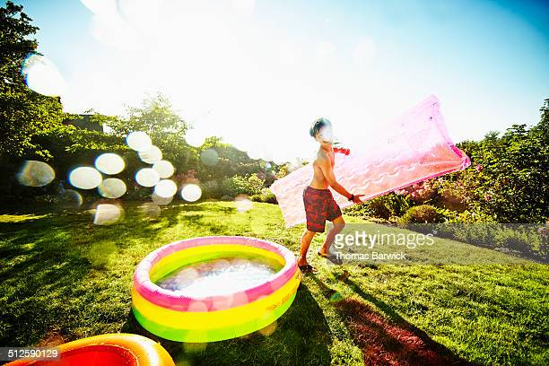 Smiling young boy running around inflatable pool