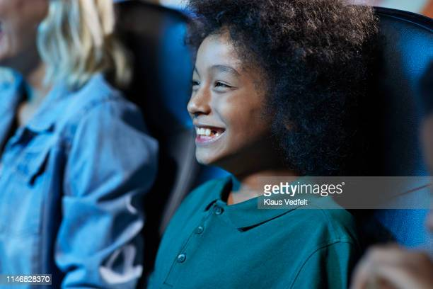 smiling young boy watching funny movie in cinema hall at theater - comedy film stock photos and pictures