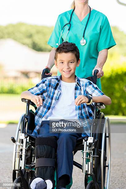 Smiling young boy with broken leg sitting in a wheelchair