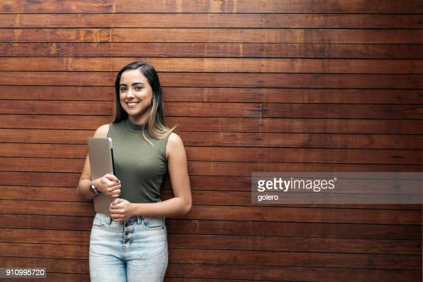 smiling young brazilian businesswoman with laptop