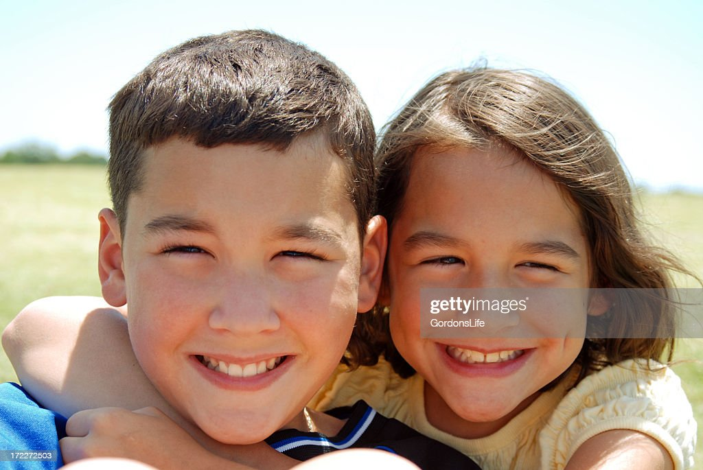 A smiling young brother and sister posing outdoors : Stock Photo