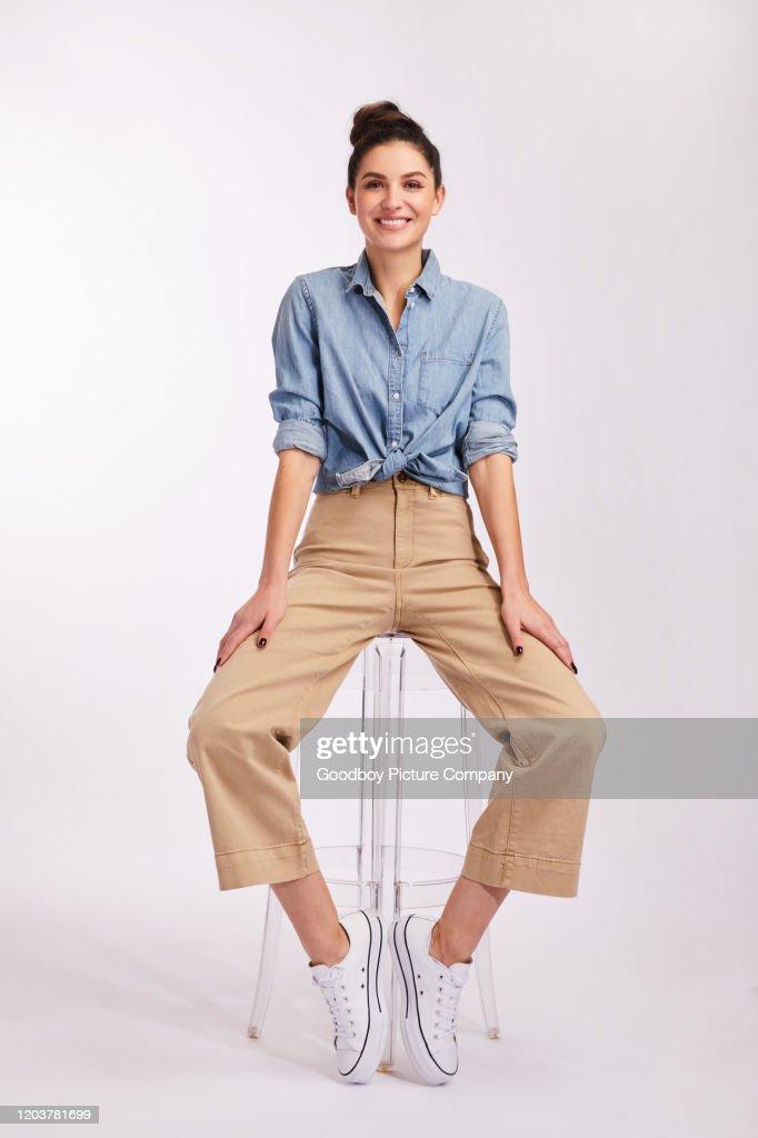 Jeune femme de brunette de sourire s'asseyant sur un tabouret sur le gris : Photo