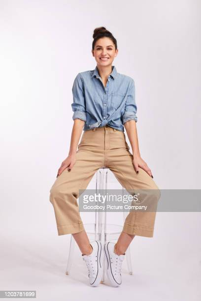 smiling young brunette woman sitting on a stool on gray - part of a series stock pictures, royalty-free photos & images