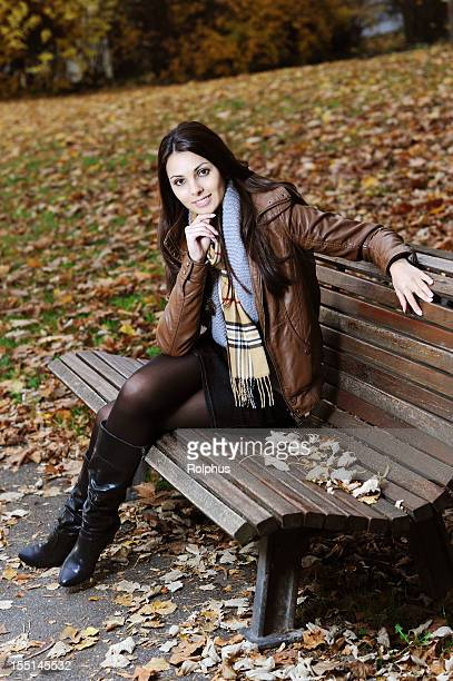 smiling young brunette woman sitting on bank fall time - leather skirt stock pictures, royalty-free photos & images