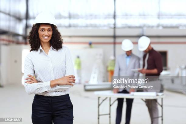 smiling young building engineer with colleagues working behind her - real estate developer stock pictures, royalty-free photos & images