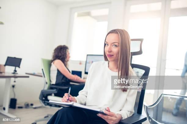 Glimlachend jonge zakelijke vrouw Neem een nota's in Office