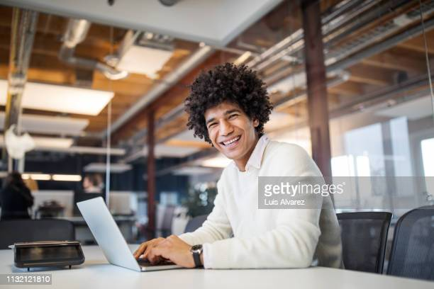 smiling young businessman at work - man in office - fotografias e filmes do acervo