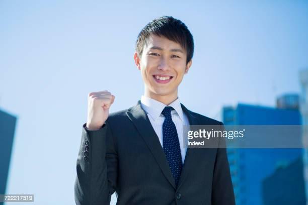 Smiling young businessman cheering