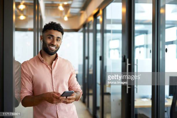 smiling young businessman holding mobile phone - indian subcontinent ethnicity stock pictures, royalty-free photos & images