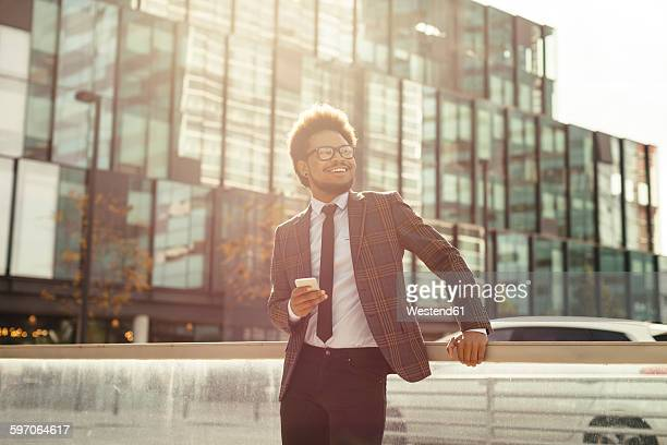 Smiling young businessman outdoors with cell phone