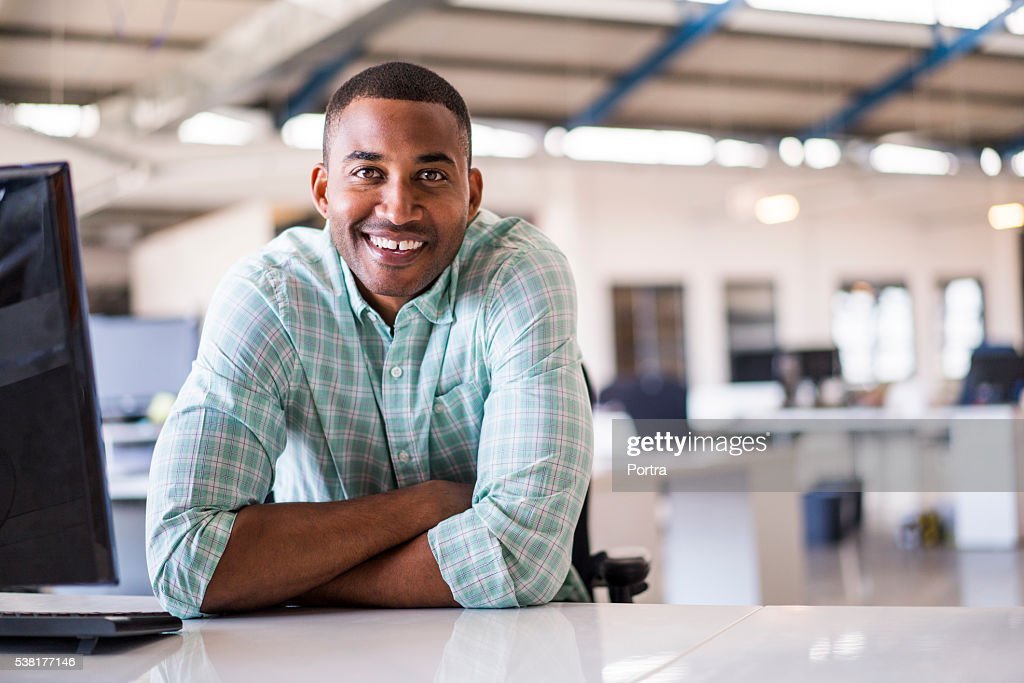 Smiling young businessman sitting at computer desk : Stock Photo