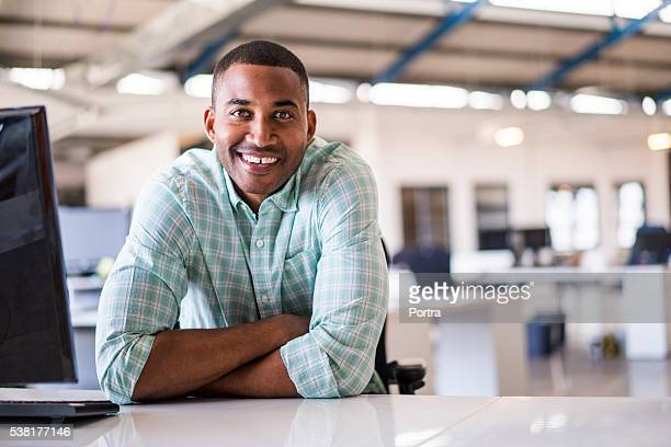 Smiling young businessman sitting at computer desk