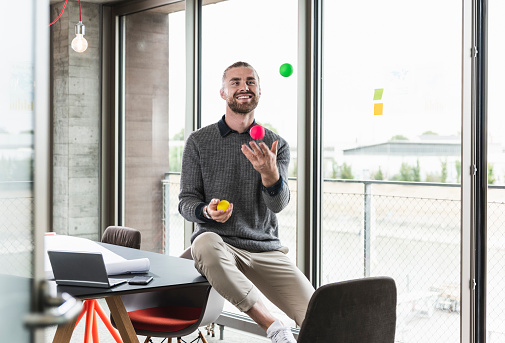 Smiling young businessman sitting at the window juggling with balls - gettyimageskorea