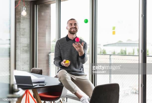smiling young businessman sitting at the window juggling with balls - jongleren stockfoto's en -beelden