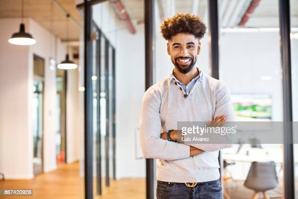 Smiling young businessman standing arms crossed in office