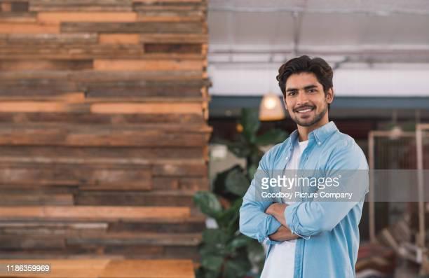 homem de negócios novo de sorriso que está em um escritório - mãos no bolso - fotografias e filmes do acervo