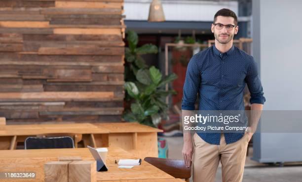 o homem de negócios novo de sorriso que está em um escritório aberto da planta - mãos no bolso - fotografias e filmes do acervo