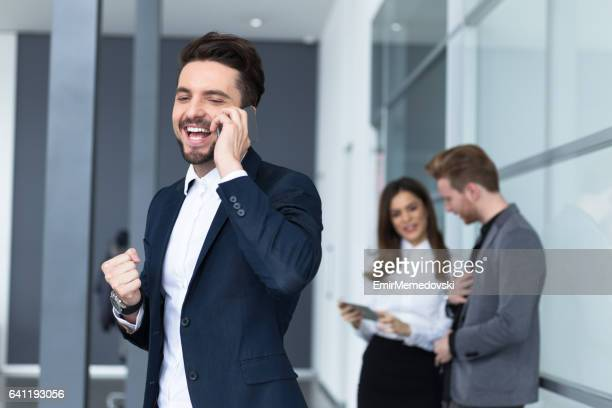 smiling young businessman talking on the mobile phone. - emir memedovski stock pictures, royalty-free photos & images