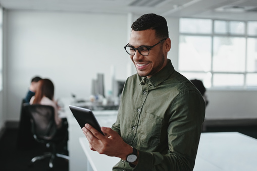 Smiling young businessman touching smartphone and checking online information in the modern office 1178146180