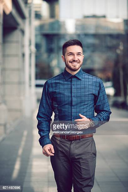 Smiling Young Businessman Walking on the City Street