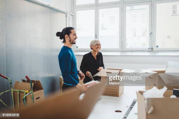 Smiling young businessman with female colleague unpacking cardboard boxes at table in new office