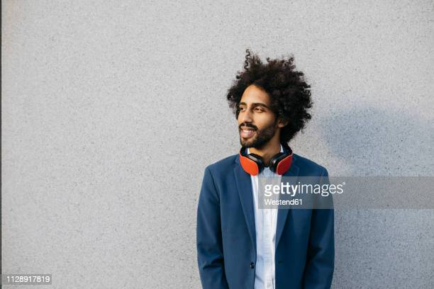 smiling young businessman with headphones at a wall - sideways glance stock pictures, royalty-free photos & images