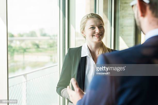 Smiling young businesswoman at the window looking at businessman