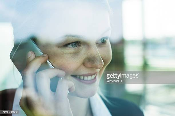 Smiling young businesswoman behind windowpane on cell phone