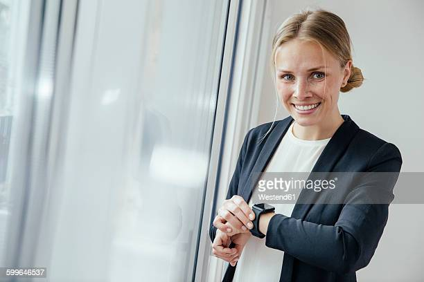 Smiling young businesswoman checking her smart watch