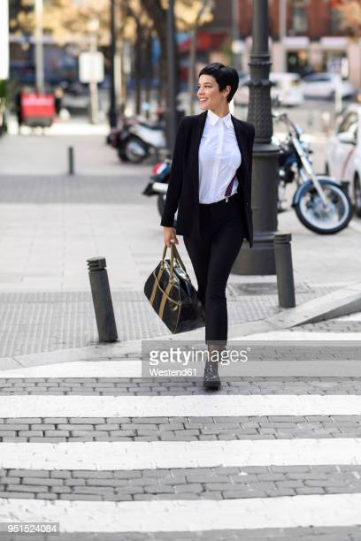 smiling young businesswoman crossing street - élégance photos et images de collection