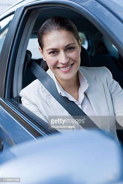 Smiling young businesswoman driving car