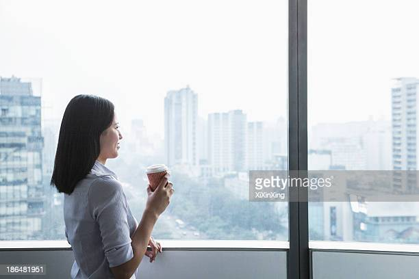 Smiling young businesswoman holding a coffee cup and looking out the window a the cityscape in Beijing, China