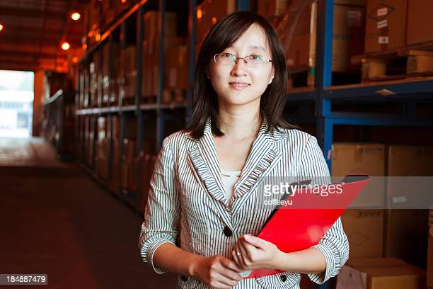 Smiling young businesswoman in warehouse