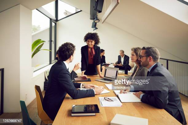 smiling young businesswoman listening to discussion of lawyers during meeting at office - law stock pictures, royalty-free photos & images