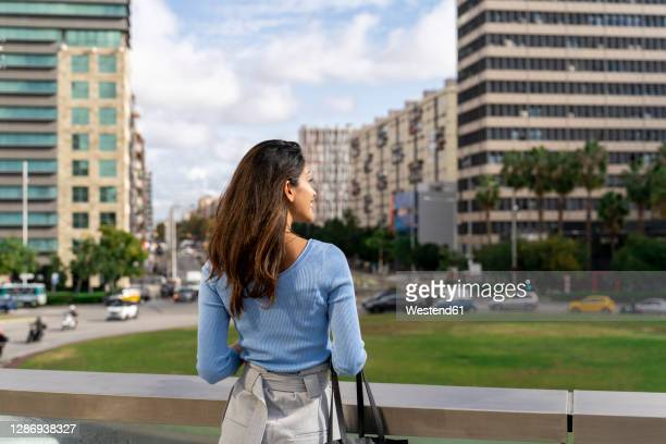 smiling young businesswoman looking at city - brown hair stock pictures, royalty-free photos & images