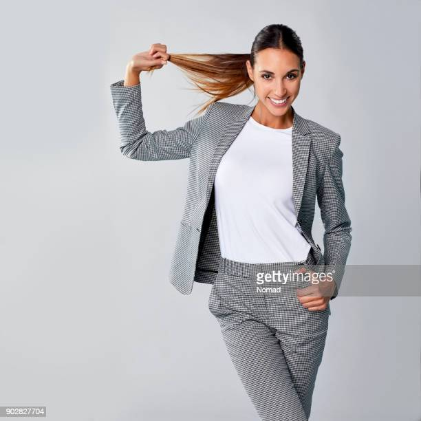 Smiling young businesswoman pulling brown hair