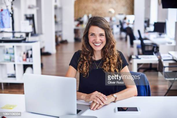 smiling young businesswoman sitting at desk with laptop in office - smart casual stock pictures, royalty-free photos & images