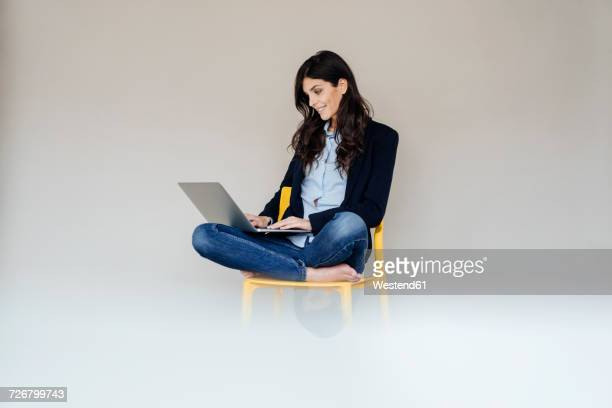 Smiling young businesswoman sitting on chair using laptop
