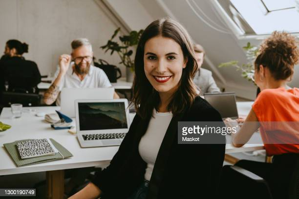 smiling young businesswoman sitting with colleagues in coworking office - personne secondaire photos et images de collection