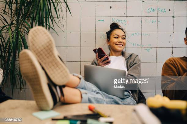 smiling young businesswoman sitting with feet up on desk using wireless technologies by colleague against wall at office - feet up stock pictures, royalty-free photos & images