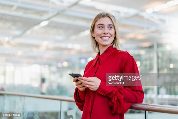 smiling young businesswoman standing at a railing with cell phone - encuadre cintura para arriba fotografías e imágenes de stock