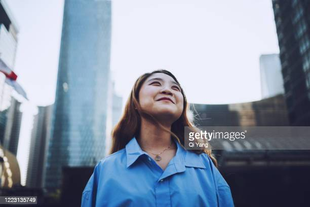 smiling young businesswoman standing in the financial district - shanghai stock pictures, royalty-free photos & images
