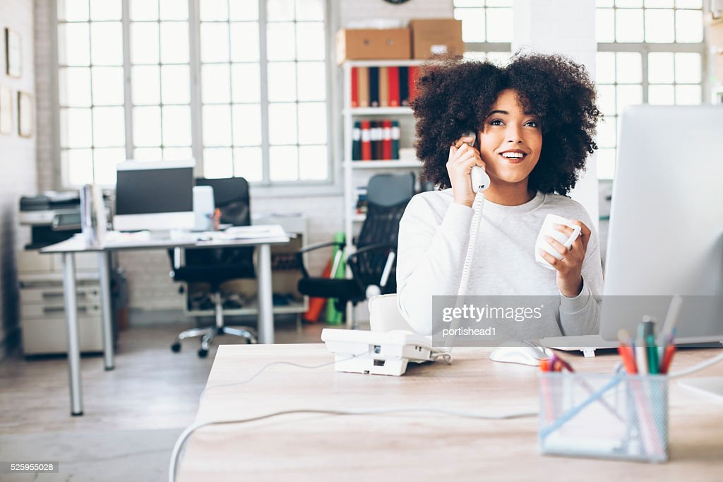 Lächelnde junge Geschäftsfrau spricht am Telefon am Arbeitsplatz : Stock-Foto