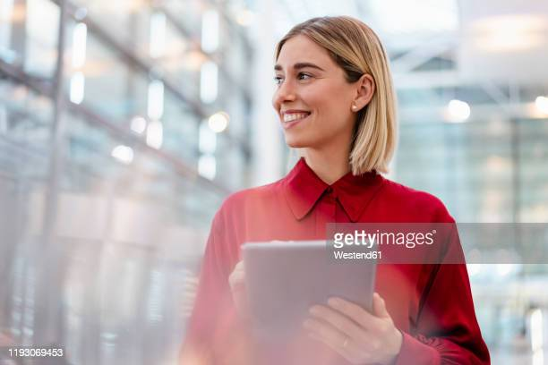 smiling young businesswoman wearing red shirt using tablet - erwartung stock-fotos und bilder