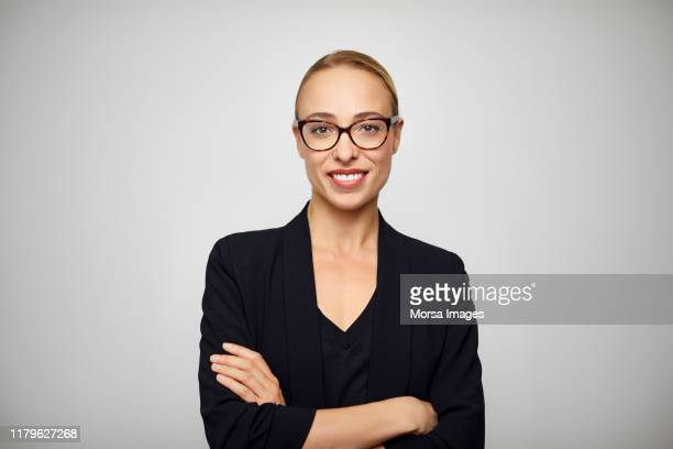 smiling young businesswoman with arms crossed - veste noire photos et images de collection