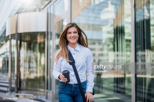 smiling young businesswoman with bag and coffee to go - shoulder bag stock pictures, royalty-free photos & images